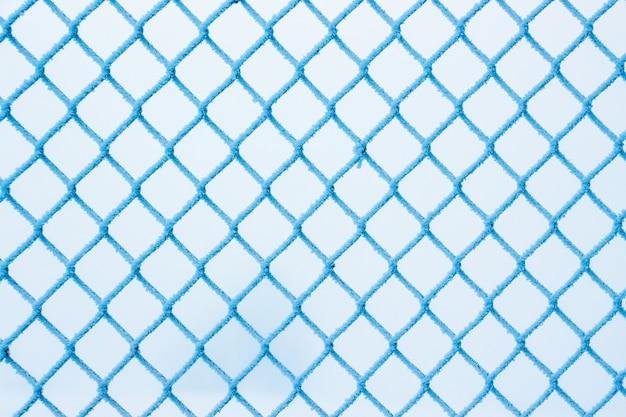 L'hiver, une grille de clôture, couverte de givre, une journée d'hiver glaciale_