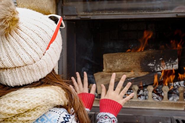 Hiver à la maison, jolie jeune fille assise près de la cheminée