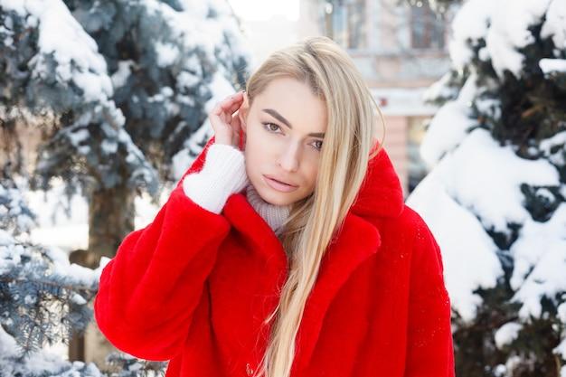 Hiver, mode, concept de personnes - mode portrait d'une belle jeune femme se promène dans la ville souriante manteau de fourrure rouge gros plan flocons de neige hiver froid, respire l'air frais au jour de gelée d'hiver. le coucher du soleil