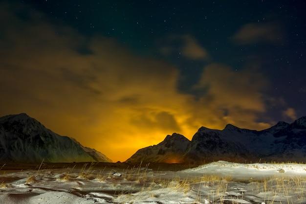 Hiver norvège. herbe couverte de neige dans la vallée de nuit. les lumières de la ville mettent en valeur les nuages derrière les montagnes