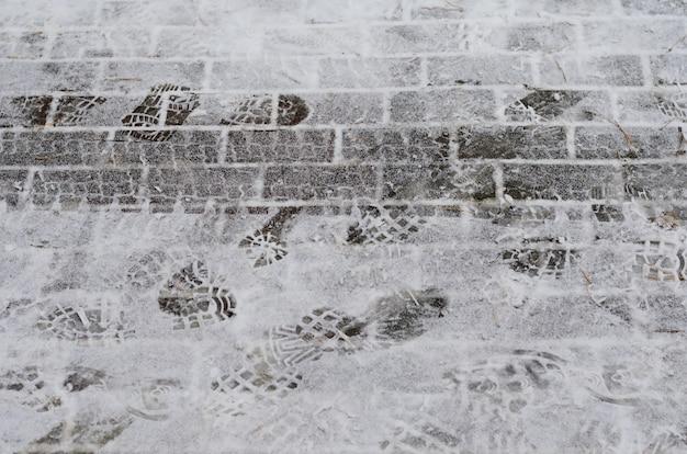 Hiver - route couverte de neige avec traces de pneus de voiture et empreintes de chaussures