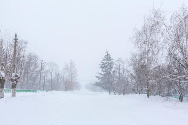 L'hiver, les rues rurales sont couvertes de neige. tempête de neige