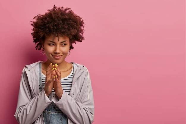 Hmm, joli plan. une femme frisée sournoise steepls les doigts, regarde mystérieusement de côté, a des pensées ou une intention délicates, veut faire quelque chose de mauvais, porte un anorak, se tient contre un mur rose pastel, espace libre