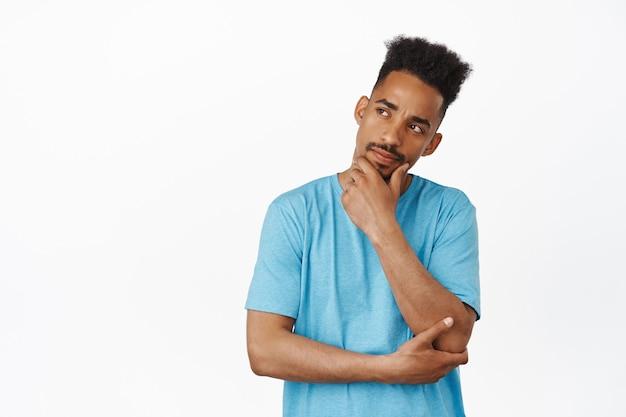 Hmm laisse-moi réfléchir. un afro-américain réfléchi touche son menton, se plisse et regarde de côté méditer sur quelque chose, prendre une décision, penser sur blanc.