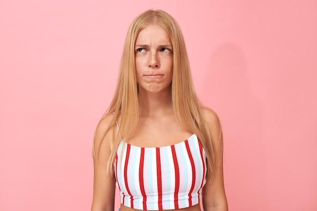 Hmm, laissez-moi réfléchir. portrait de jeune femme se mordant les lèvres, regardant vers le haut avec une expression pensive, ayant de nombreux doutes
