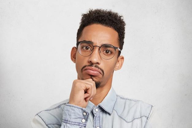 Hmm pas mal. close up portrait en studio de gestionnaire masculin sérieux concentré ou patron évalue le travail d'autres personnes