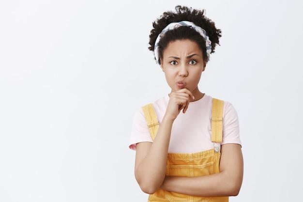 Hmm, question difficile. portrait de la pensée douteuse créative et mignonne fille afro-américaine en bandeau et salopette, tenant la main sur le menton, pincer les lèvres et lever un sourcil, prendre une décision