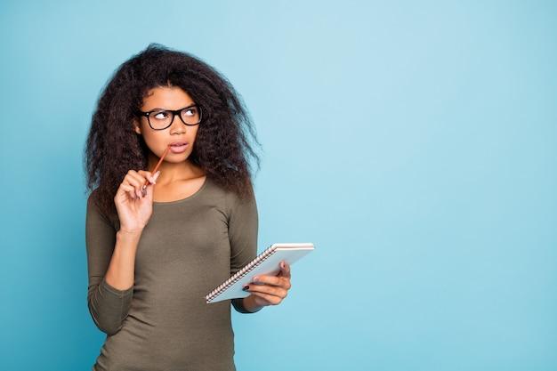 Hmm quoi créer? portrait of smart smart smart mulâtre girl hold pen écrire dans le carnet de notes journal pense que les pensées portent une tenue élégante isolée sur un mur de couleur bleu