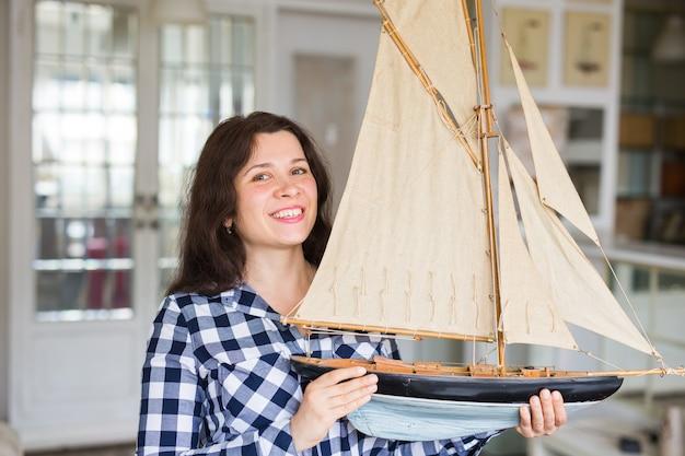 Hobby, intérieur et concept de collecte - jeune femme tenant la disposition d'un voilier dans la chambre
