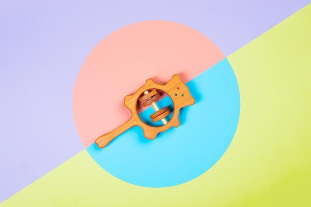 Hochet en bois de hêtre sur un fond géométrique vibrant multicolore isolé.