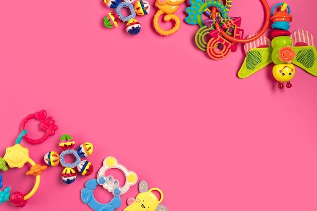 Hochet pour enfants en plastique sur fond rose. vue de dessus. espace de copie. mise à plat