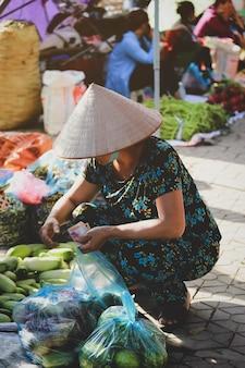 Hoi an, vietnam - 7 juillet 2019 : vietnamiens achetant des légumes au marché du matin à hoi an, vietnam