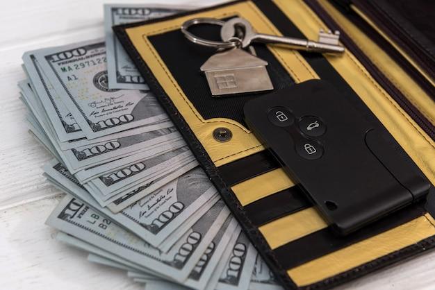 Homa nad clés de voiture avec des billets d'un dollar sur la table. concept d'économie