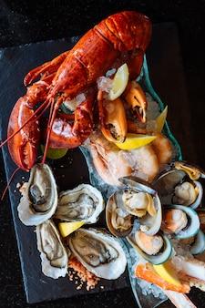 Homard bouilli, huîtres fraîches, crevettes, moules et palourdes servies dans une assiette en pierre noire.