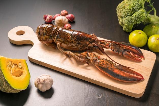 Homard canadien cru, homard cru entier. écrevisses sur la plaque de bois carrée sur une surface en bois.