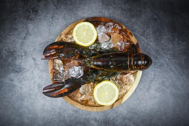 Homard frais dans le restaurant de fruits de mer pour plats cuisinés / homard cru sur glace et citron sur une vue de dessus de table en pierre noire
