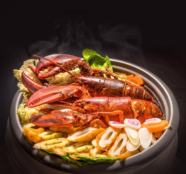 Homard nabe, homard servi chaud avec des légumes dans une casserole, homard servi dans un plat chaud avec légumes et viande.