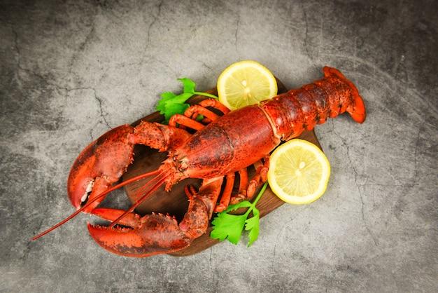 Homard rouge aux légumes et citron sur une planche à découper en bois, vue de dessus - dîner au homard
