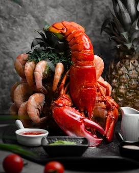 Homard servi avec crevettes tigrées et sauces
