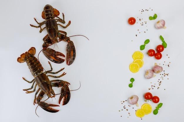 Homards non cuits isolés sur une surface blanche avec des épices