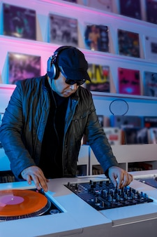 Hombre dj mezclando musica en un tornamesa con discos de vinil y escuchando en los audifonos
