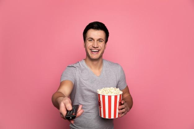 Home cinéma. homme heureux en tenue décontractée, qui tient une télécommande dans sa main droite et un tube de pop-corn dans sa main gauche et souriant.