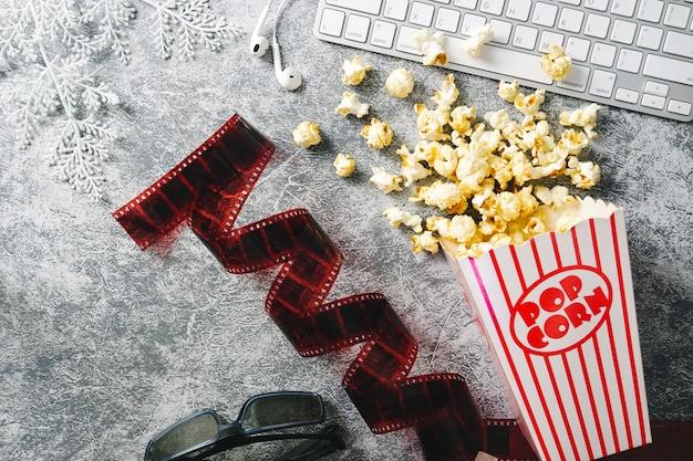 Home cinéma popcorn caramel dans des gobelets en papier lunettes 3d et loft backgroundflim 35mm.