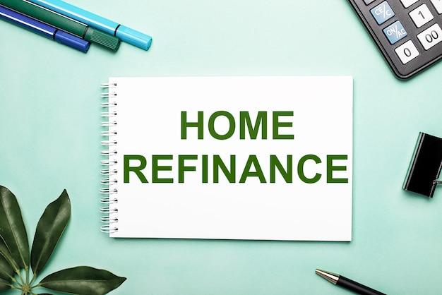 Home refinance est écrit sur une feuille blanche sur fond bleu près de la papeterie et de la feuille sheffler. appel à l'action. concept de motivation