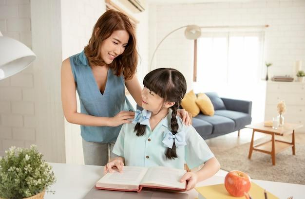Homeschool asiatique petite jeune fille étudiant l'apprentissage assis sur une table travaillant avec son tuteur à la maison.