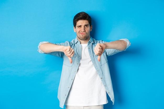 Un homme de 25 ans sceptique et déçu en tenue décontractée n'aime pas quelque chose de mal, montrant les pouces vers le bas et grimaçant mécontent, debout sur fond bleu