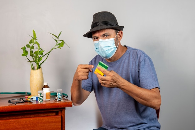 Homme de 59 ans prenant des médicaments pour prendre soin de sa santé physique, utilisant un masque et un chapeau