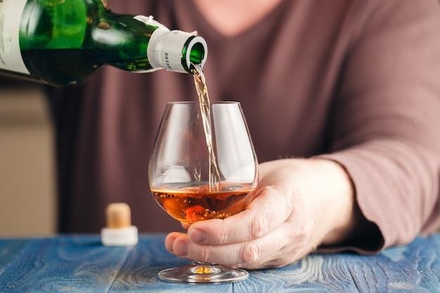 Homme abusant de l'alcool pour se détendre, whisky en verre