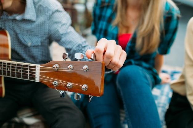 Homme accordant la guitare. gros plan du manche. passe-temps de loisirs de musique. vocation d'interprète
