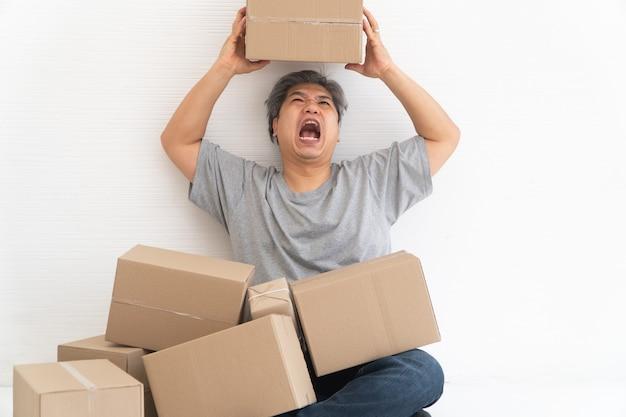 Homme accro du shopping asiatique choqué et assis sur le sol