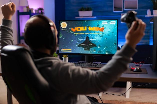 Homme accro jouant au jeu vidéo de tir spatial à l'aide d'écouteurs et d'une console sans fil. un joueur enthousiaste levant la main après avoir remporté un match de championnat en ligne dans un studio de jeu à domicile