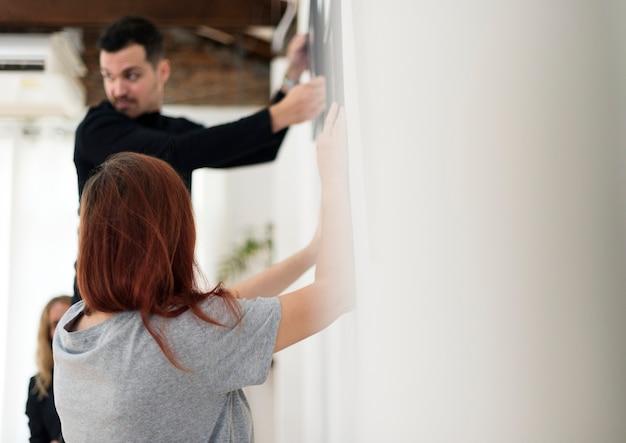 Un homme accrochant le cadre photo sur le mur