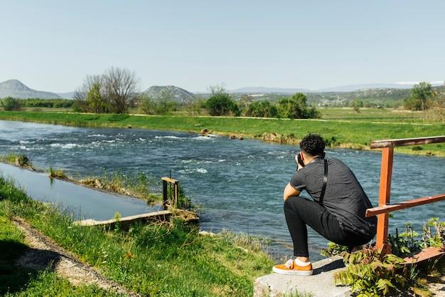 Homme accroupi prenant une photo de la rivière idyllique