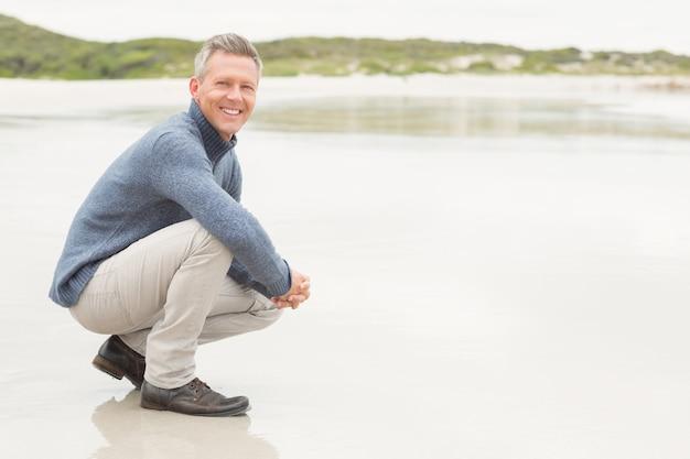 Homme accroupi sur la rive