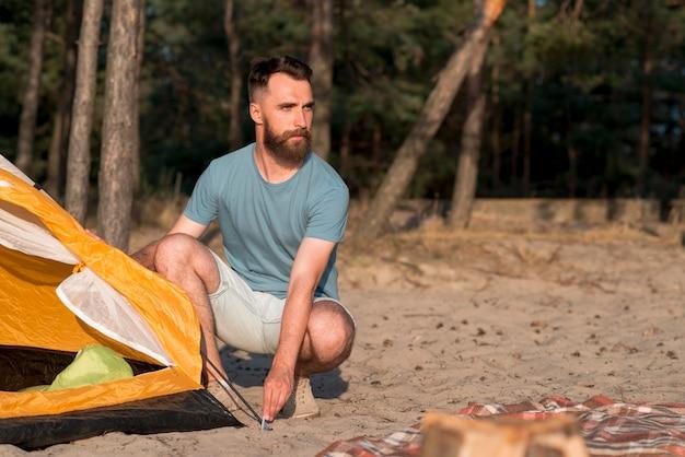 Homme accroupi en train d'installer la tente