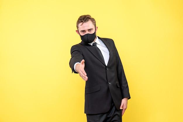 L'homme accueille les partenaires commerciaux sur jaune