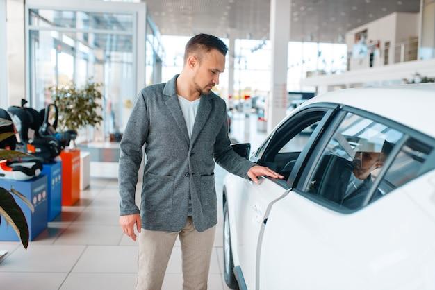 Homme achetant une nouvelle voiture dans la salle d'exposition.