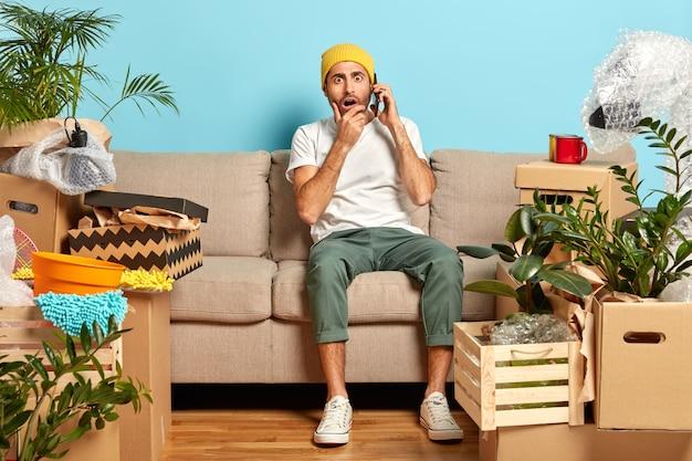 Un homme acheteur de maison a acheté une nouvelle maison, appelle quelqu'un via un smartphone moderne, a une expression stupéfaite