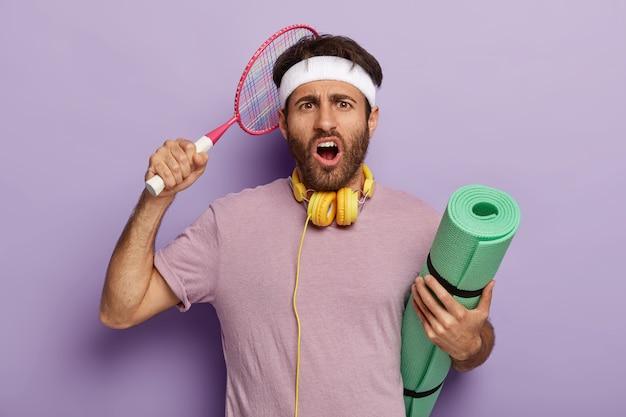 Homme actif bouleversé posant avec des équipements sportifs