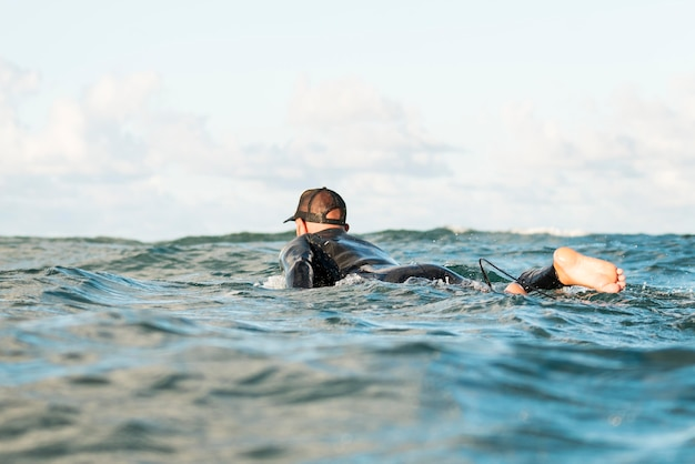 Homme actif dans un équipement spécial restant sur une planche de surf