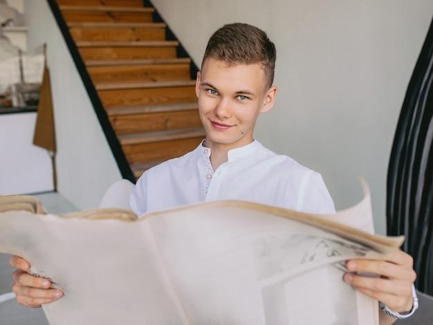 Homme adolescent moderne lisant le journal papier pendant le petit-déjeuner à la maison