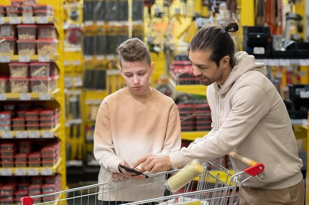 Homme et adolescent regardant à travers des produits en ligne dans un smartphone sur un panier