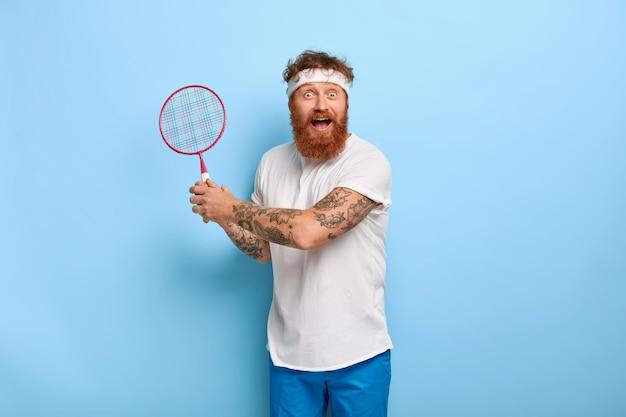Homme adulte actif émotif avec des cheveux roux détient une raquette de badminton, regarde joyeusement la caméra
