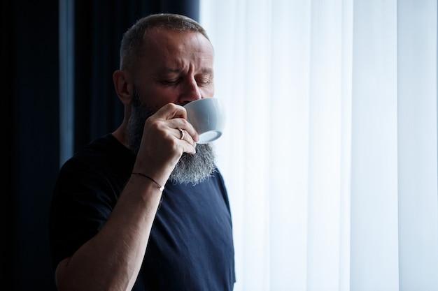 Un homme adulte avec une barbe boit du café et regarde par la fenêtre. concept de loisirs sur le terrain de la journée de travail