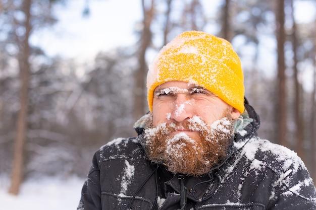 Un homme adulte avec une barbe dans une forêt d'hiver tout le visage dans la neige, gelé, mécontent du froid