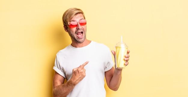 Homme adulte blond à l'air excité et surpris en pointant sur le côté avec un milk-shake